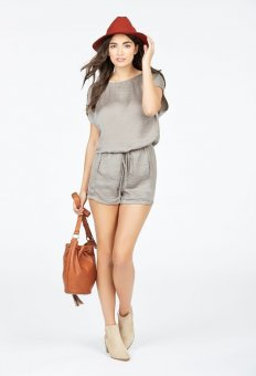 a lady wearing a short-sleeved satin playsuit and beige ankle shoes, holding a brown neck bag.