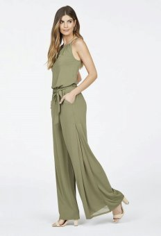 a lady putting on an olive-coloured broad knee jumpsuit and heeled sandals.